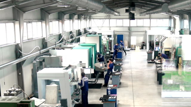 Metal processing plant timelapse. Wide angle timelapse of a modern metal processing plant with multiple CNC machines and workers walking. HD 1080p computer aided manufacturing stock videos & royalty-free footage