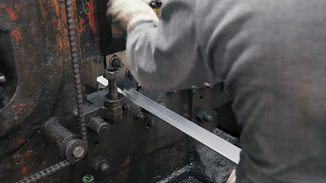 Metal punching machine cut angle steel by Hydraulic Ironworker in factory. Old industry concept.