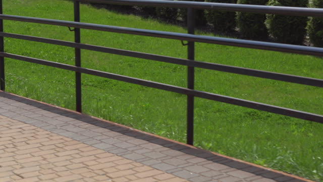 Metal railing fencing in a city park along a footpath and green grass on a sunny day. The camera moves along the fence Metal railing fencing in a city park along a footpath and green grass on a sunny day. The camera moves along the fence railing stock videos & royalty-free footage