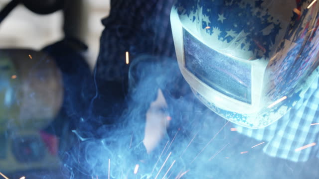 Metal shop worker american flag helmet Welder with American Flag welding helmet face mask works with Mig Arc Welder to weld American Steel and throw lots of bright sparks in slow motion. work helmet stock videos & royalty-free footage