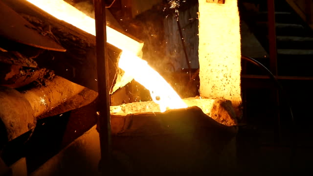 Metal Stream Flows Slowly with Sparks Puffs into Tank