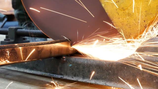 metallarbeiter schleifen eisen mit elektrischem sah während der arbeit in einer werkstatt - kreissäge stock-videos und b-roll-filmmaterial