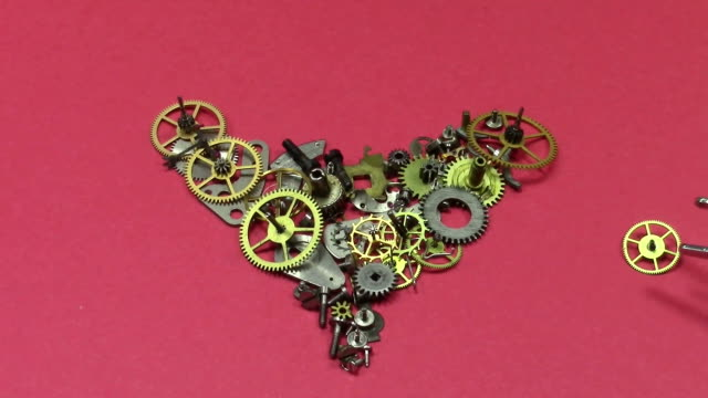 Metallic toothed wheels and small pieces from dismantled clocks arranged in the shape of a heart on red background , one piece attached with tweezers video