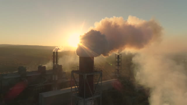metallurgical production smoke emits from the factory pipe. top view of heavy industry plant smoking smokestacks at sunset - metallurgia video stock e b–roll