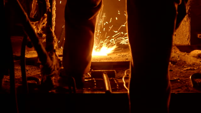 Metallurgist at work by the blast furnance, iron and steel works Worker by the blast furnance at a metallurgical plant steel mill stock videos & royalty-free footage