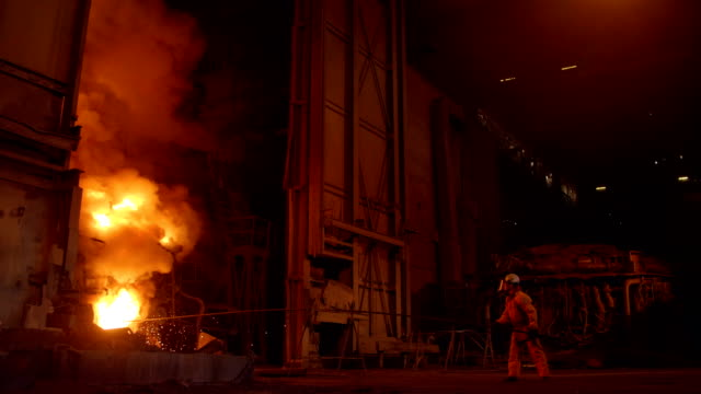 Metallurgist at work by the blast furnance, iron and steel works video