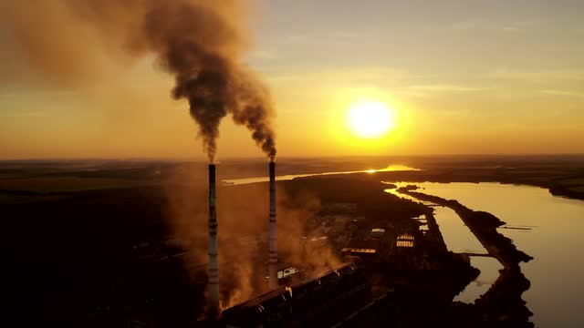 Metallurgy plant in nature at orange sunset. Metallurgy plant in nature at orange sunset. Dark smoke of industrial factory pollute the atmosphere. Evening background of a factory near the river. metallurgy stock videos & royalty-free footage
