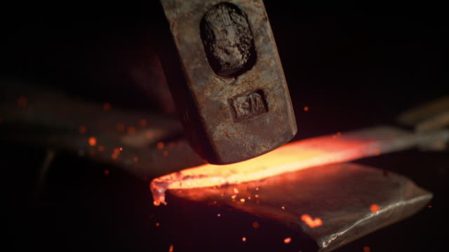 SUPER SLOW MOTION: Metalworker forging a hot piece of metal into a knife blade. SUPER SLOW MOTION, MACRO, DOF: Metalworker forging a hot piece of metal into a beautiful knife blade. Cinematic shot of a glowing blade getting struck by a large hammer. Craftsman manufacturing blade. anvil stock videos & royalty-free footage