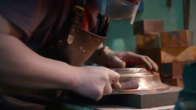 Metalworks. Close-up video of the hands of the man wearing the leather apron who polishing the copper detail in the workshop.