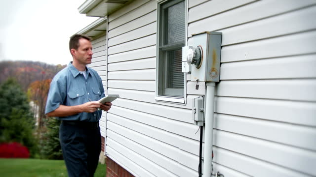 Meter Reader A utility worker inspects an electrical meter on a house. quality control stock videos & royalty-free footage