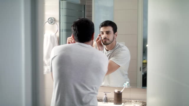Metrosexual Man Trimming Eyebrows For Body Care In Bathroom Handsome man with beard grooming in bathroom at home for morning routine and body care. Caucasian metrosexual person trimming eyebrow with tweezers vanity stock videos & royalty-free footage