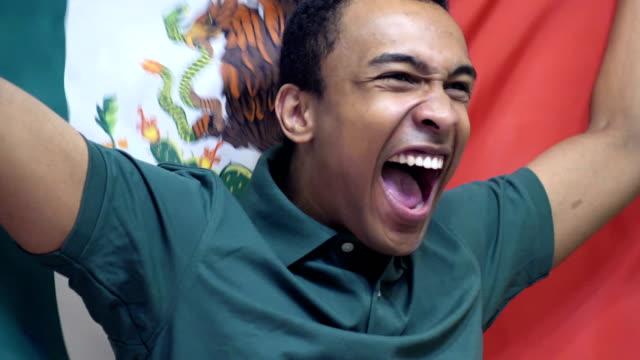 vídeos de stock e filmes b-roll de mexican fan celebrating while holding the flag of mexico in slow motion - liga desportiva
