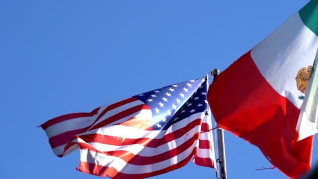 mexikanska flaggan flyger bredvid den amerikanska flaggan - frame bildbanksvideor och videomaterial från bakom kulisserna