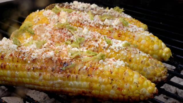mexican lime street corn with cotija cheese and chili powder - kukurydza zea filmów i materiałów b-roll