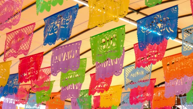 Mexican papel picado flying in the wind Mexican papel picado flying in the wind. Mexican fiesta background with colorful perforated paper carnival celebration event stock videos & royalty-free footage