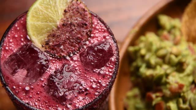 vidéos et rushes de cocktail mexicain de margarita de fraise et guacamole avec des croustilles de tortilla - pamplemousse