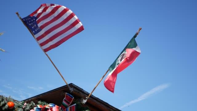 meksykańska trójkolorowa i amerykańska flaga machająca na wietrze. dwie narodowe ikony meksyku i stanów zjednoczonych przeciw niebu, san diego, kalifornia, usa. polityczny symbol granicy, relacji i współpracy - american flag filmów i materiałów b-roll