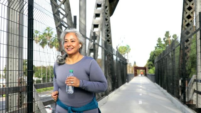 mexikanische frau joggen auf einem trail - aktiver lebensstil stock-videos und b-roll-filmmaterial