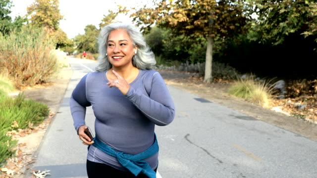 donna messicana che fa jogging - donne mature video stock e b–roll