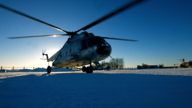 Mi-8 helicopter during the parking Mi-8 helicopter during the parking, spinning blades. snowy weather. medevac stock videos & royalty-free footage