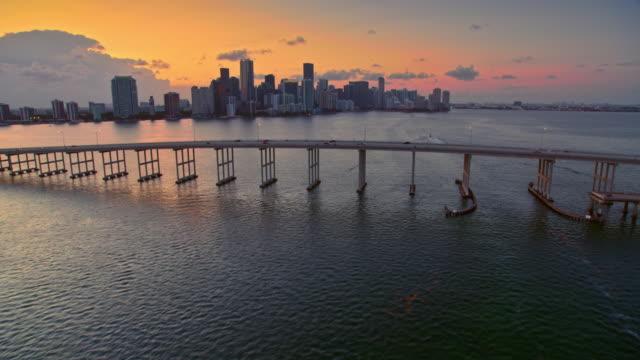 aerial miami skyline at sunset from the rickenbacker causeway - most konstrukcja wzniesiona przez człowieka filmów i materiałów b-roll