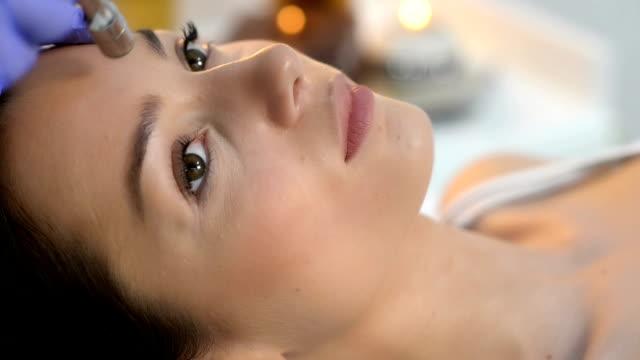 mikrodermabrasion im schönheitssalon - kosmetische behandlung stock-videos und b-roll-filmmaterial