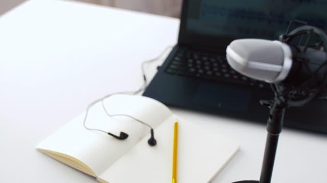mikrofon, bärbar dator, hörlurar på antecknings bok på bordet video