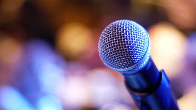 microphone on a blue-violet and yellow-orange background - cantante video stock e b–roll