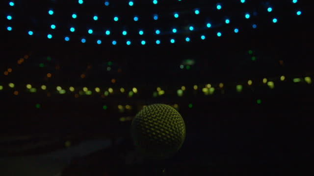 Microphone on a stage.  Blue and green spotlights video