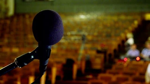 mikrofon auf einem vor einem leeren saal - zuschauerraum stock-videos und b-roll-filmmaterial