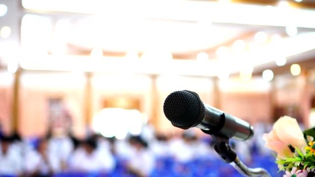 mikrofon auf abstrakter verwischung der sprache im seminarraum oder sprechenden konferenzsaal licht auf der bühne mit blumen, event-hintergrund. business talk präsentationskonzept - zuschauerraum stock-videos und b-roll-filmmaterial