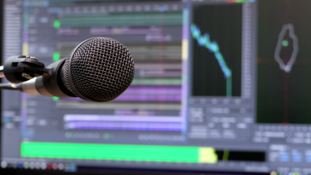 Microphone on the background of the computer monitor. Home recording Studio. Close-up. The focus in the foreground. Blurred background. Software for recording and editing sounds. 4K, UHD, Ultra HD video