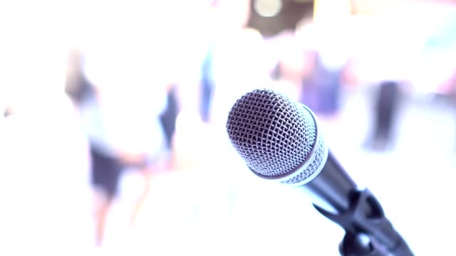 vídeos de stock e filmes b-roll de microphones on abstract blurred of speech in seminar room, speaking conference hall light for presentation in exhibition event background. mic is transducer that convert sound into electrical signal. - training