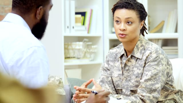 Mid adult African American female veteran discusses issues with mental health professional Female military veteran discusses issues with a male mental health professional. The mental health professional ask her a question. She gestures while responding to his question. veteran stock videos & royalty-free footage