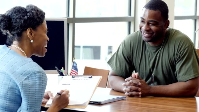Mid adult African American soldier applies for a loan at a local bank Mature female loan officer reviews a military soldier's loan application. They talk with each other about the loan terms and conditions. veteran stock videos & royalty-free footage