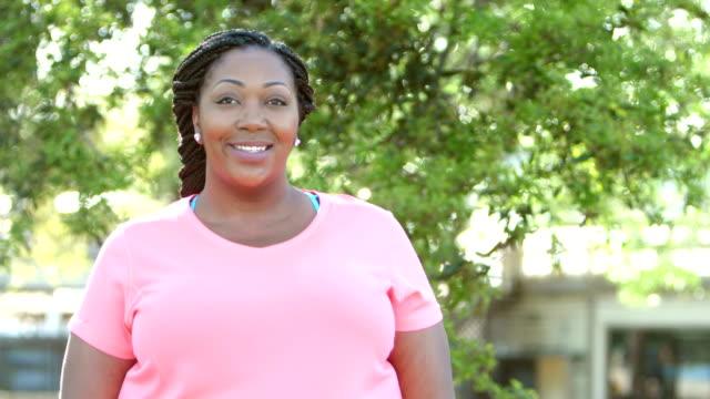 vídeos de stock, filmes e b-roll de meados adulta mulher afro-americana, em pé ao ar livre - camiseta preta