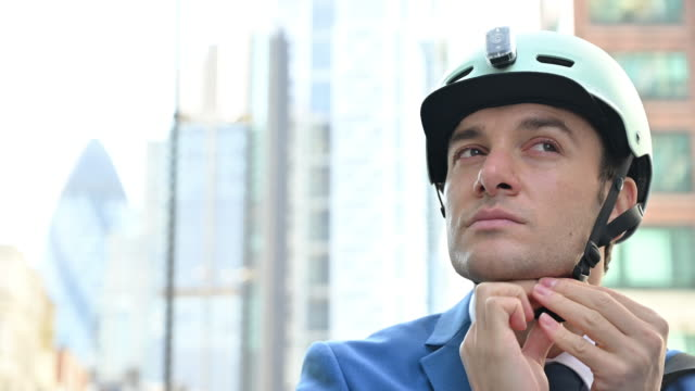 Mid adult businessman putting on helmet and cycling away