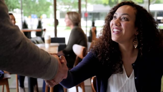 Mid adult businesswoman greets male colleague in coffee shop