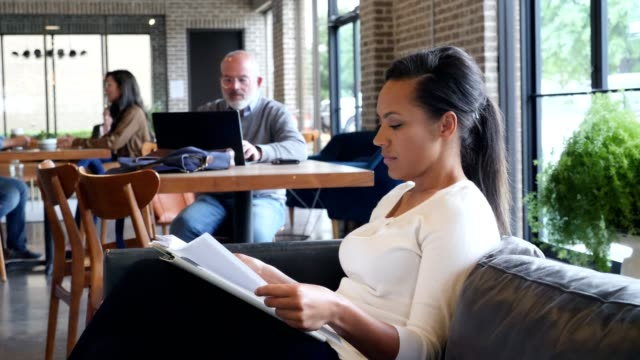 Mid adult businesswoman reviews document while in coffee shop Confident mid adult African American businesswoman examines a document while working from a coffee shop before work. She is sitting on a sofa in the coffee shop. coffee shop stock videos & royalty-free footage