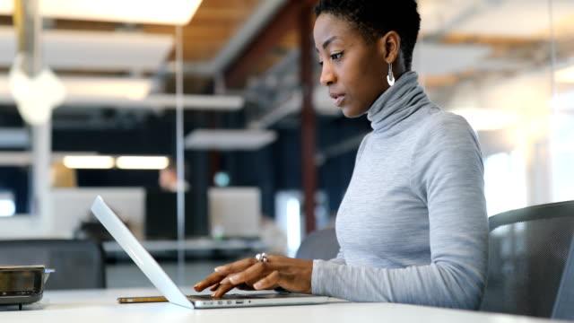 mitten av vuxen affärskvinna med laptop i nya office - använda en dator bildbanksvideor och videomaterial från bakom kulisserna
