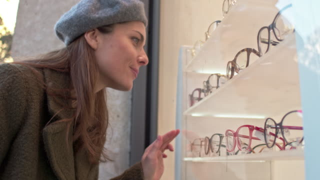 Mid adult caucasian woman looking for eyeglasses at window store video