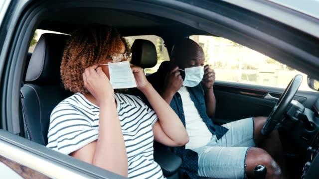 mittlere erwachsene paar setzen auf schützende gesichtsmasken im auto - krankheitsverhinderung stock-videos und b-roll-filmmaterial