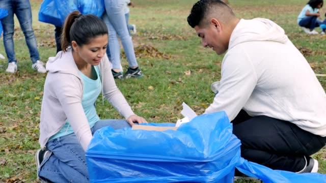vídeos y material grabado en eventos de stock de medio par adultos trabajen juntos durante el día de la limpieza de comunidad - servicios sociales