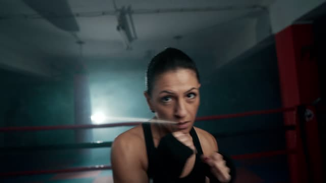 mid adult female boxer shadow boxing - kick boxing video stock e b–roll