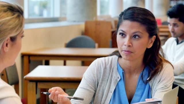Colegio femenino adulto medio los estudiantes estudian juntos para un examen - vídeo