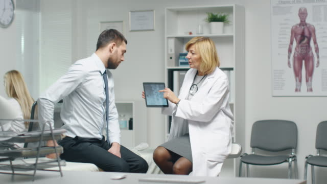 Mid Adult Female Doctor Consults Young Man About His Back Pain. Doctor Shows Him Tablet Computer With His Spine X-Ray. video