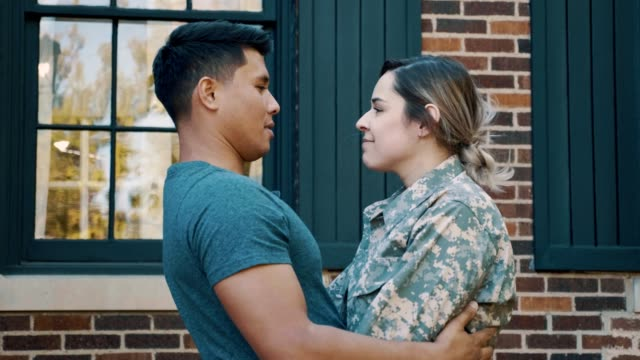 mid adult husband tells his military wife goodbye as she leaves for deployment - moglie video stock e b–roll
