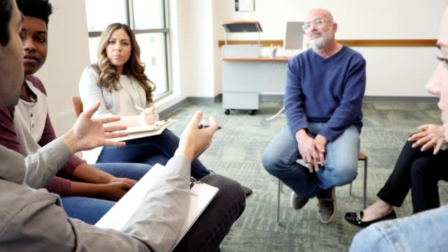 Mid adult male therapist facilitates support group Male therapist gestures as he gives advice to a group of people during a support group meeting. psychiatrist stock videos & royalty-free footage
