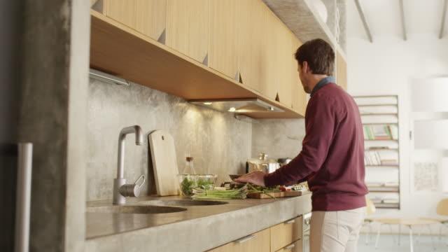 Homme d'âge adulte mi cuisson des aliments au comptoir de la cuisine - Vidéo