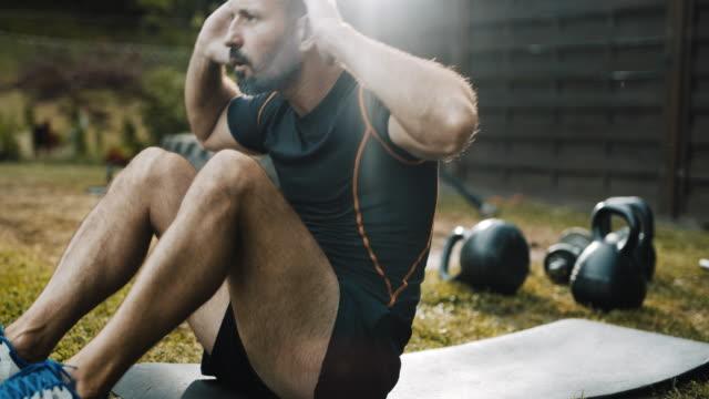 裏庭で座っているdsミッドアダルトマン - クロストレーニング点の映像素材/bロール